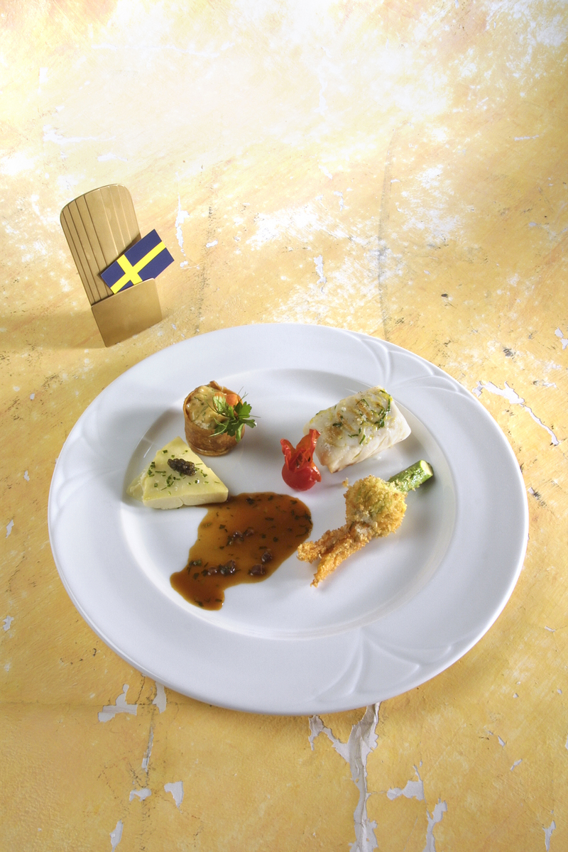 Pavé de bar aux Saint-Jacques et truffes sur lit de fenouil. Gâteau de pommes de terre rempli d'une purée de chou-fleur couronnée de caviar. Fleur de courgette farcie de bar aux truffes. Ragoût de homard aux herbes fraîches, vinaigrette de homard aux oliv