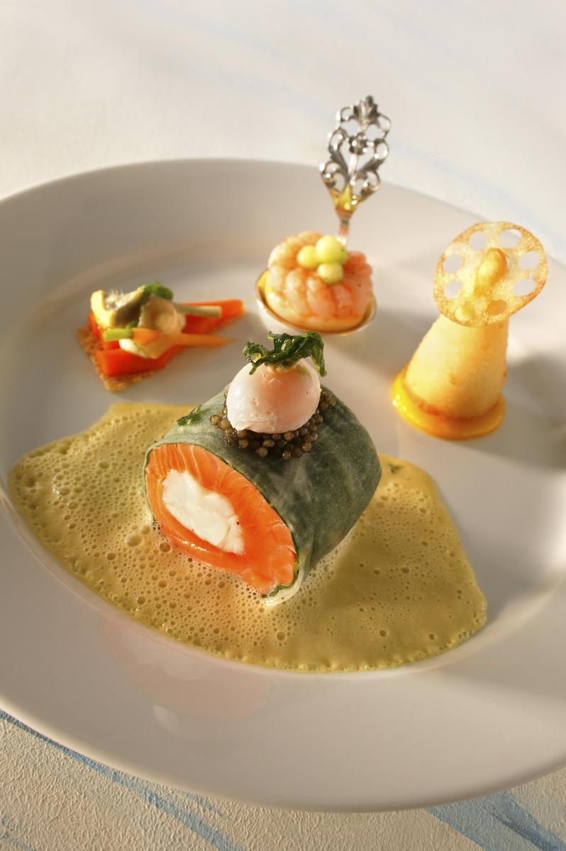 Langoustine enveloppée dans une Truite des Fjords de Norvège infusée au citron et estragon. Flan de crevettes aux huîtres et sevruga. Ganache de pommes de terre en croûte croustillante. Légumes. Bruchetta. Emulsion de coco-agrumes-curry